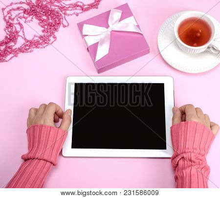 Two Female Hands In A Pink Sweater Are Holding An Electronic Tablet With An Empty Black Screen Over