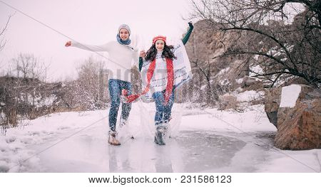 Young Couple Has Fun In Park And Rides On Frozen Puddle Covered With Melted Water. Water Splashes Fl