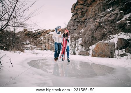 Young Couple With Cups Of Hot Tea In Their Hands Hold Hands, Smile And Walking Across Puddle Of Melt