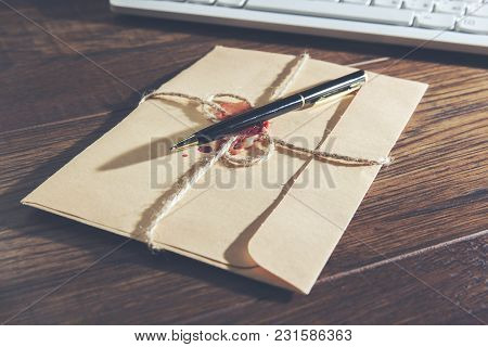 Letter And  Keyboard With Pen On Brown Desk