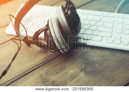 Headphones With Keyboard On Table Close Up