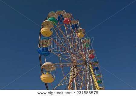 Ferris Wheel Against The Blue Sky In The City Park
