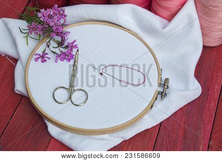 Red And Pink Thread And White Fabric In The Wooden Embroidery Frame For Needlework, A Workplace For
