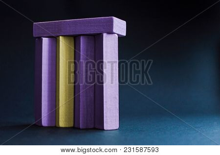 Yellow Wood Bar Besieged With Violet Wood Bars On The Dark Blue Background. Concept Of The Racism, S