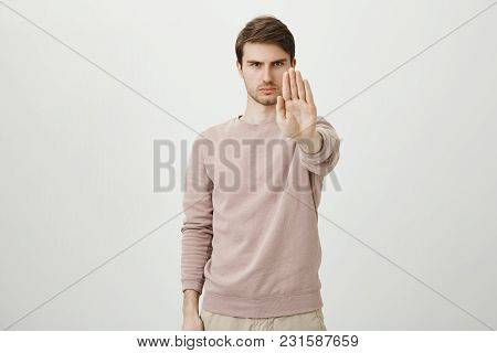 Portrait Of Calm Serious Young Man With Bristle Stretching Hand Towards Camera With Stop Or Hold Ges