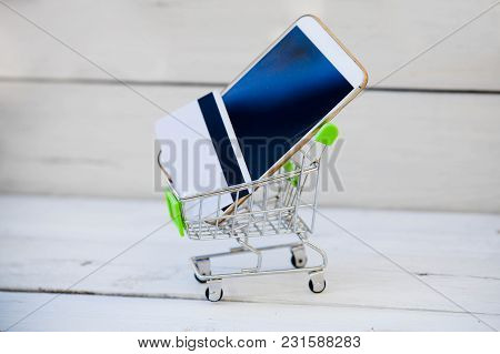 Closeup Of Smartphone In Shopping Cart On Wooden Table Background