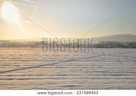 Slovak Houses And Villageat Sunset  In Winter. Snow-covered  Field In Sunny Day  With Village And Hi