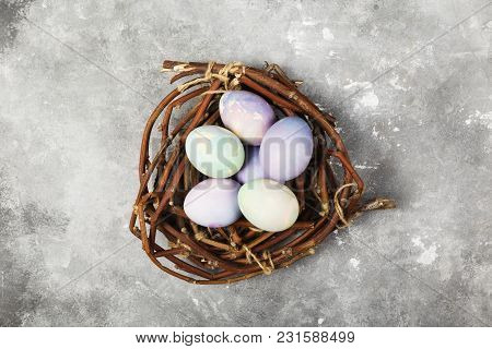 Multicolored Eggs For Easter In Nest On Gray Background. Top View. Food Background