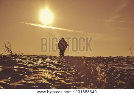 Silhouette Of A Walking Hunter At Sunset On The Snowy Hill With Gun In Winter Time. Silhouette Of Yo