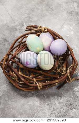 Multicolored Eggs For Easter In Nest On Gray Background. Top View, Copy Space. Food Background