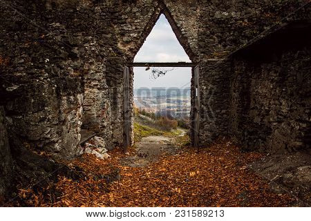 Image Of Opened Castle Gate With Beautiful View From Arched Passage With Leafs On The Floor In Autum