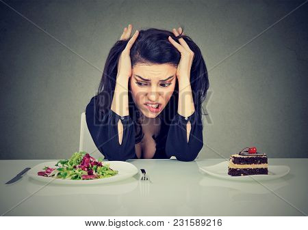 Young Woman Craving For Cake Having Problems With Diet Choice Sitting With Plates Of Salad And Cake.