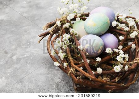 Multicolored Eggs For Easter In Nest With Flowers On Gray Background. Copy Space. Food Background