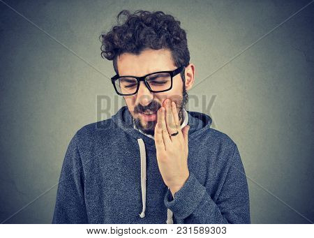 Young Man With Tooth Ache Suffering From Pain, Touching Outside Mouth With Hand