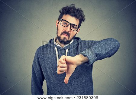 Young Man In Eyeglasses Showing Dislike With Thumb Down Gesture Looking At Camera And Frowning.