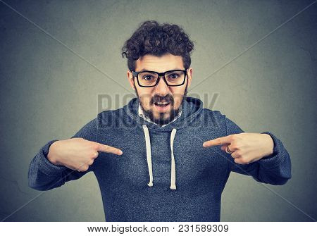 Young Angry Man In Eyeglasses Overreacting While Pointing At Himself Looking Offended.
