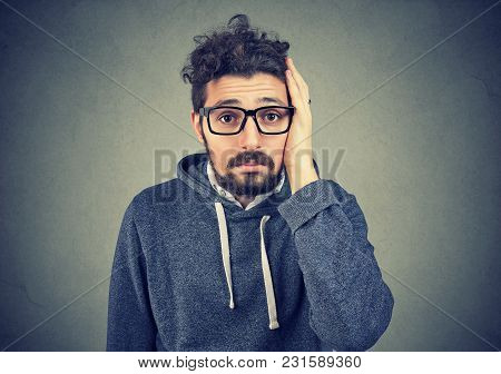 Portrait Of Disappointed Stressed Bearded Young Man On A Gray Background. Negative Human Emotions