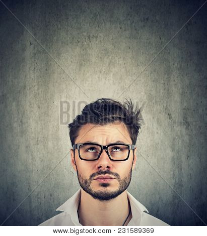 Portrait Of A Young Doubtful Man With Glasses Looking Up