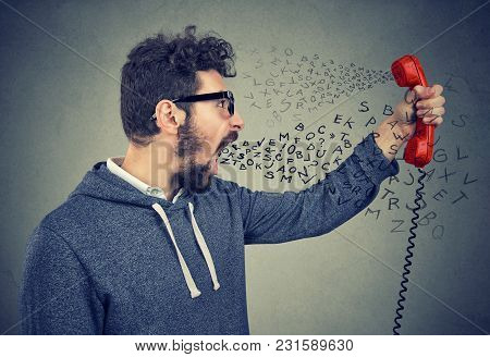 Side Profile Of An Angry Man Screaming At Someone On Telephone Handset With Alphabet Letters Flying
