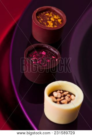 Assortment Of Luxury White And Dark Chocolate Candies Variety On Purple And Red Plate