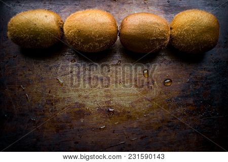 Four Fruits Of Ripe Kiwi Are Displayed In The Top Row On A Worn, Vintage, Dark And Shabby Background
