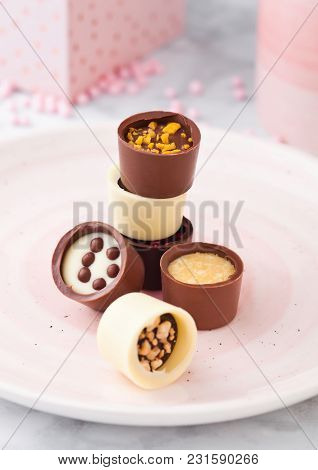 Assortment Of Luxury White And Dark Chocolate Candies Variety On Pink Plate With Cup And Gift Box