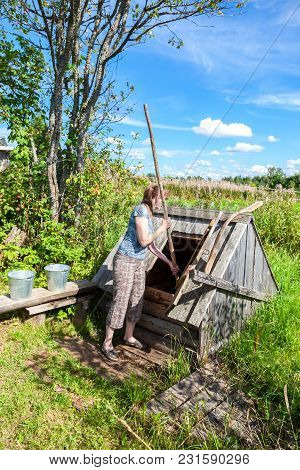 Young Attractive Woman Near The Wooden Water Well In The Village In Summer Sunny Day