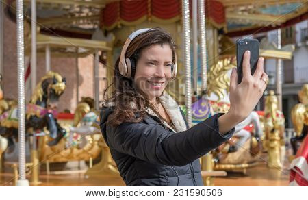 joy, woman next to a merry-go-round taking selfie with the cell phone on a spring afternoon. image of freshness and lifestyle in europe