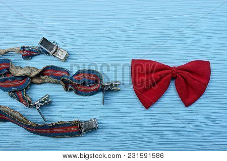 Red Bow Tie And Old Suspenders On A Blue Table