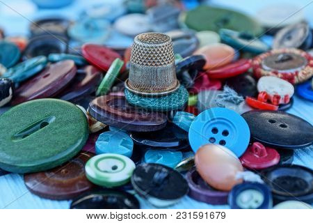 Thimble And A Pile Of Colored Buttons On The Table