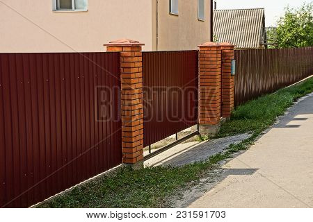 Metal Fence Of Red Color Near The Road