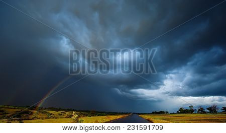 Rainbow In The Field Rain And Dark Clouds. Spring Season, Evening. Panoramic And Web Banner.
