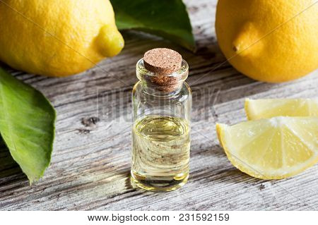 A Bottle Of Lemon Essential Oil With Fresh Lemons On A Table