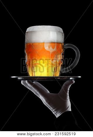 Hand With Glove Holds Tray With Glass Of Beer With Foam And Bubbles On Black Background