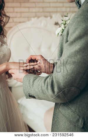 A Closeup View Of Bride And Groom Exchanging Rings, Vertical Image