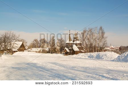 Gold Ring Of Russia. Winter Rural Landscape With Log Houses And Wooden Church