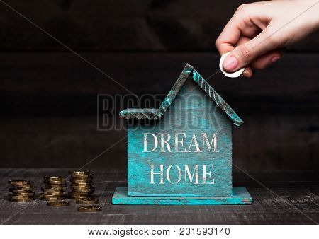 Wooden House Model With Coins Next To It And Hand Holding The Coin With Conceptual Text. Dream Home