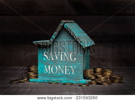 Wooden House Model With Coins Next To It With Conceptual Text. Saving Money