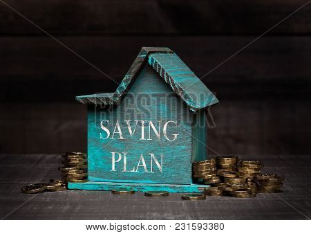 Wooden House Model With Coins Next To It With Conceptual Text. Saving Plan
