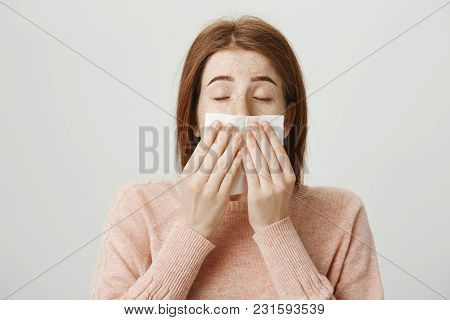 Close-up Portrait Of Cute Redhead European Woman With Freckles Sneezing Or Blowing Out Nose In Napki