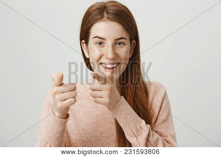 Close-up Portrait Of Cute Happy Redhead Caucasian Woman Pointing At Camera With Index Fingers, Smili