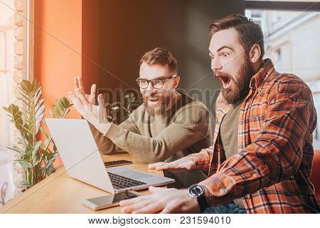 Very Emotional Picture Of Guys Looking To The Laptop's Screen. One Of Them Is Very Amazed And Opened