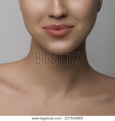 Close Up Of Dissatisfied Lips. The Young Woman With Pure Leather Squeezes Lips, A Grin With Natural