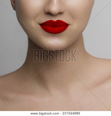 Macro Shot Of A Beautiful Face Of The Woman Squeezing Lips. Pure Leather And Brightly Red Lipstick.