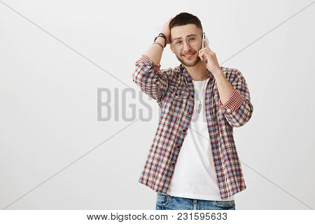 Confused Attractive European Guy Talking On Cellphone While Touching Head And Smiling Anxiously, Exp
