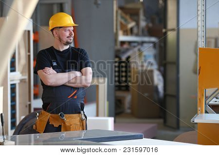 Portrait Of Young Attractive Man In Work Clothes And Yellow Helmet Crossed Arms Smiling At Shop For