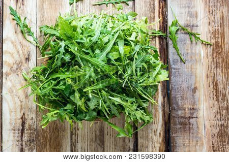 Fresh Arugula Leaves On Wooden Bowl, Rucola. Arugula Rucola On Wooden Old Background. Arugula Rucola