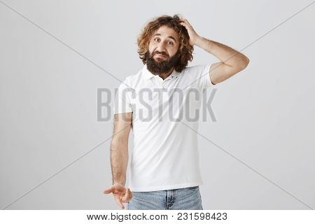 Man In Not Sure He Bought What Wife Asked. Portrait Of Uncertain Questioned Eastern Guy With Curly H