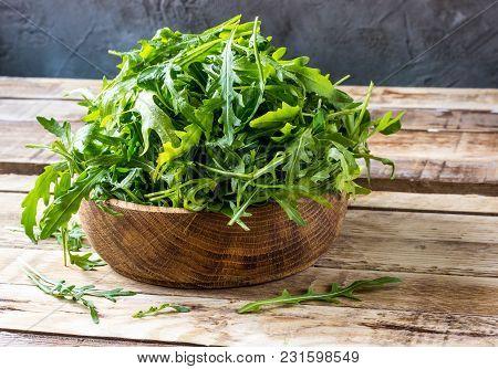 Fresh Arugula Leaves On Wooden Bowl, Rucola. Arugula Rucola On Wooden Old Background. Arugula Rucola