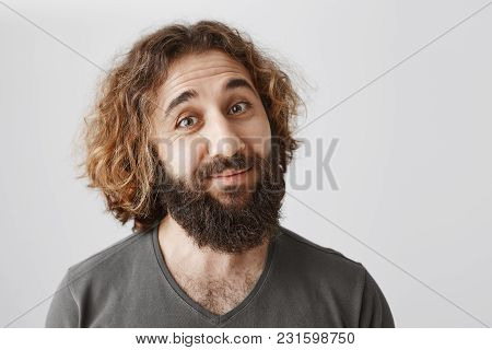 Indoor Portrait Of Doubtful Polite Eastern Guy With Beard Tilting And Lifting Eyebrows In Disbelief,